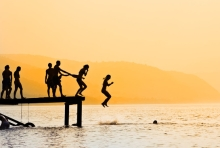 Silhouettes of kids who jump off dock on the lake
